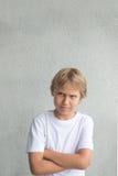 Niño con los brazos cruzados Muchacho con la camiseta blanca que se coloca cerca de la pared gris Fotografía de archivo