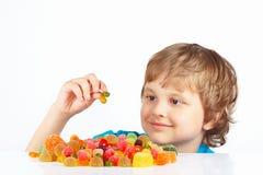 Niño con los dulces y los caramelos en el fondo blanco Fotos de archivo libres de regalías