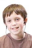 Niño con los earbuds Fotografía de archivo