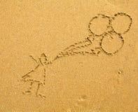 Niño con los globos que dibujan en la arena imagenes de archivo