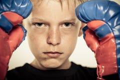 Niño con los guantes de boxeo y la expresión seria Imágenes de archivo libres de regalías