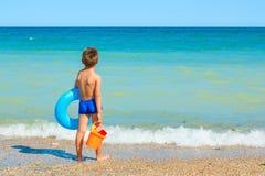 Niño con los juguetes, mirando el mar fotos de archivo libres de regalías