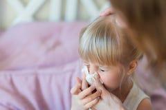 Niño con los mocos Mime a ayuda soplar la nariz del ` s del niño con el tejido de papel Enfermedad estacional Imagen de archivo