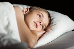 Niño con los ojos abiertos con la cabeza en la almohada Fotos de archivo
