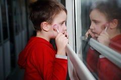 Niño con los ojos soñadores que hacen frente hacia fuera a la ventana de un tren. fotos de archivo libres de regalías