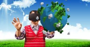 Niño con los vidrios virtuales detrás de una tierra 3D con el fondo del cielo Imágenes de archivo libres de regalías