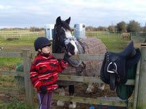 Niño con montar a Pony In Field imagen de archivo