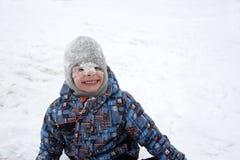 Niño con nieve en cara Imagenes de archivo