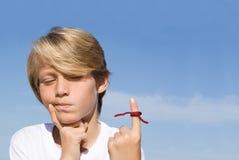Niño con recordatorio atado cadena Imagen de archivo