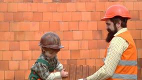 Niño con su padre en el casco que juega las unidades de creación Hijo que ayuda a su padre a construir la pared Poco albañil del  almacen de metraje de vídeo