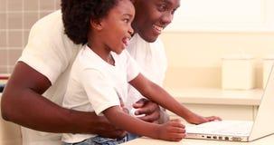 Niño con su usar del padre video en línea en el ordenador almacen de metraje de vídeo