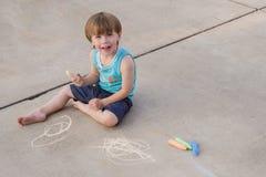 Niño con tiza de la acera Imagen de archivo