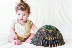 Niño con un casco militar Fotografía de archivo