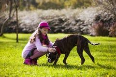 Niño con un perro del boxeador Imagen de archivo