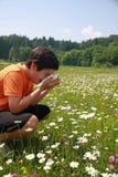 Niño con una alergia al polen mientras que estornudo en el medio del th Fotos de archivo libres de regalías