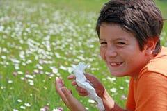 Niño con una alergia al polen mientras que estornudo en el medio del th Imagenes de archivo