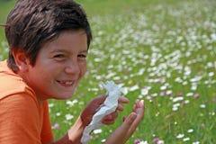 Niño con una alergia al polen mientras que estornudo en el medio del th Foto de archivo