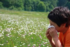 Niño con una alergia al polen mientras que usted sopla su nariz con a Fotos de archivo