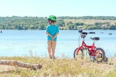 Niño con una bicicleta cerca del río Fotos de archivo libres de regalías