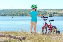 Niño con una bicicleta cerca del río Foto de archivo