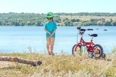 Niño con una bicicleta cerca del río Imagen de archivo