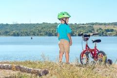 Niño con una bicicleta cerca del río Fotografía de archivo libre de regalías