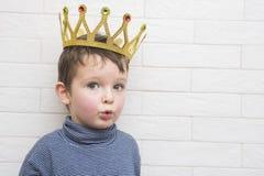 Niño con una corona de oro en su cabeza contra un fondo de la pared de ladrillo fotografía de archivo