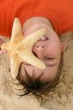 Niño con una estrella de mar grande Imágenes de archivo libres de regalías