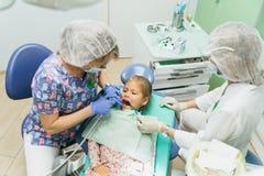 Niño con una madre en una recepción del ` s del dentista El doctor trabaja con un ayudante Hay una operación para llenar imágenes de archivo libres de regalías
