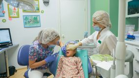 Niño con una madre en una recepción del ` s del dentista La muchacha miente en la silla, detrás de su madre El doctor trabaja con Fotos de archivo