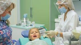 Niño con una madre en una recepción del ` s del dentista La muchacha miente en la silla, detrás de su madre El doctor trabaja con Imagenes de archivo