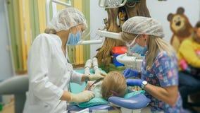 Niño con una madre en una recepción del ` s del dentista La muchacha miente en la silla, detrás de su madre El doctor trabaja con Foto de archivo