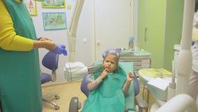 Niño con una madre en una recepción del ` s del dentista La muchacha miente en la silla, detrás de su madre El doctor trabaja con almacen de metraje de vídeo