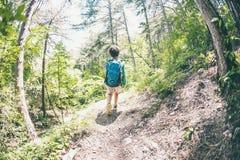 Niño con una mochila en el bosque Imagen de archivo