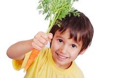 Niño con una zanahoria a disposición fotografía de archivo