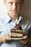 Niño confuso con la torta de cumpleaños Imagen de archivo