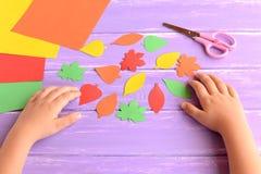Niño cortado de las hojas de otoño del papel coloreado Niño que hace los artes de papel del otoño Arte y arte de la educación pre fotos de archivo