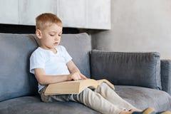 Niño creativo asombroso brillante que lee un libro Foto de archivo