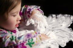 Niño creativo que juega con la espuma blanca Fotografía de archivo libre de regalías