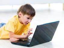 Niño curioso con la computadora portátil Foto de archivo libre de regalías