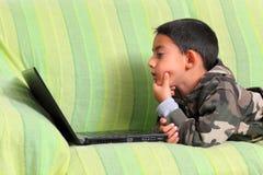 Niño curioso con la computadora portátil Imagenes de archivo
