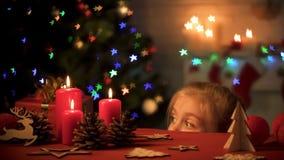 Niño curioso que mira la tabla con los juguetes de madera hechos a mano, atmósfera festiva fotos de archivo