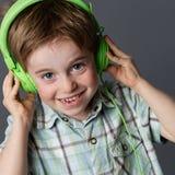 Niño dañoso con las pecas que ríe, escuchando la música Foto de archivo libre de regalías