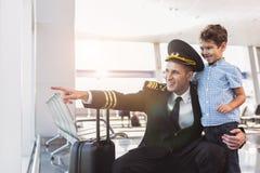 Niño de abarcamiento del aviador alegre del papá Foto de archivo