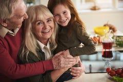 Niño de abarcamiento encantado de los pares mayores en cocina Foto de archivo libre de regalías