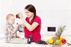 Niño de alimentación de la madre en cocina Imagen de archivo