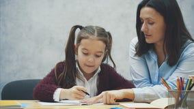 Niño de ayuda del profesor joven que escribe la lección o madre e hija que aprenden escribir, niña de enseñanza de la madre almacen de metraje de vídeo