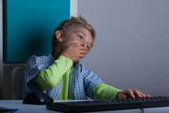 Niño de bostezo usando el ordenador Imagen de archivo libre de regalías