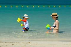 Niño de dos años que juega con la madre en la playa Foto de archivo