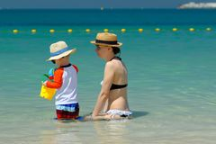 Niño de dos años que juega con la madre en la playa Imagen de archivo libre de regalías